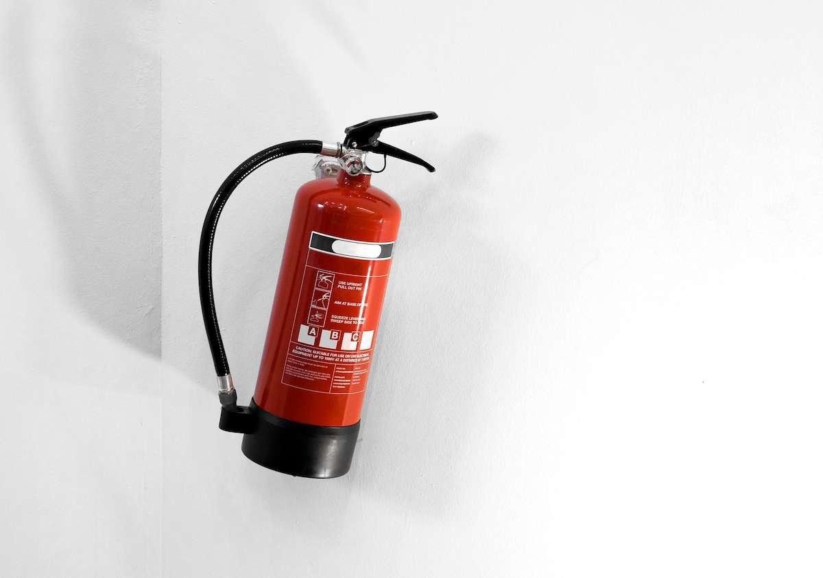 Extintor instalado en una pared blanca